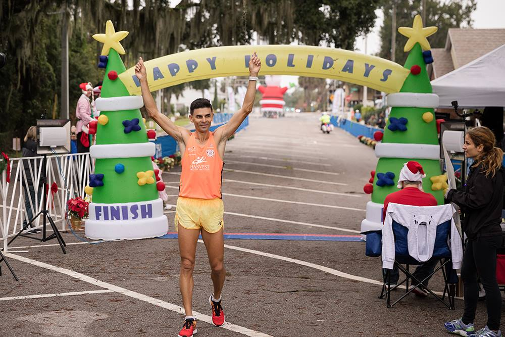 man crossing Mount Dora 5K finish line